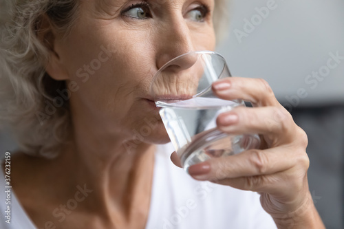 Canvastavla Close up thirsty beautiful middle aged woman drinking fresh pure mineral water,