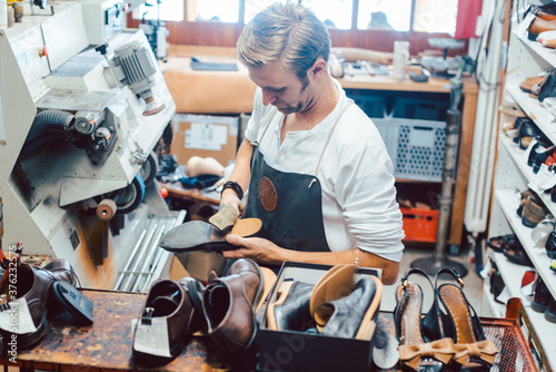 Fotografie, Obraz Shoemaker with shoes to repair on a rack in his workshop