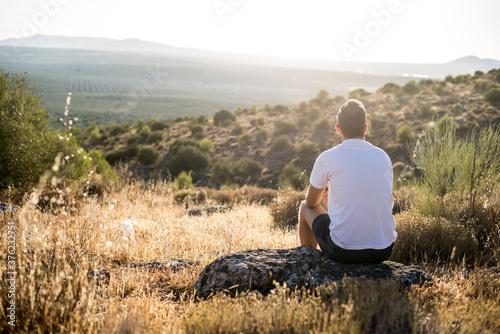 Obraz na plátně Persona sentada en una piedra en el campo mirando al horizonte y disfrutando de la naturaleza