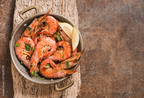 Fototapeta Shrimps delicious meal served in copper pan copy space. obraz