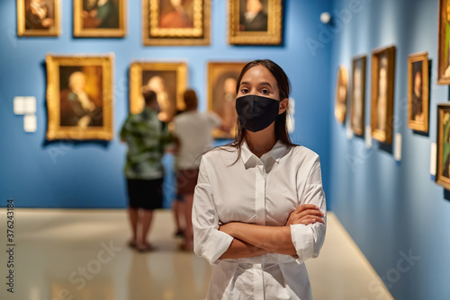 Woman visitor wearing an antivirus mask in the historical museum looking at pictures Tableau sur Toile