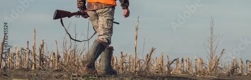 Fotografía Hunter man in rural field with shotgun and backpack during hunting season