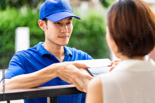 Asian deliver man hadling package and wait customer acknowledge sign Canvas Print