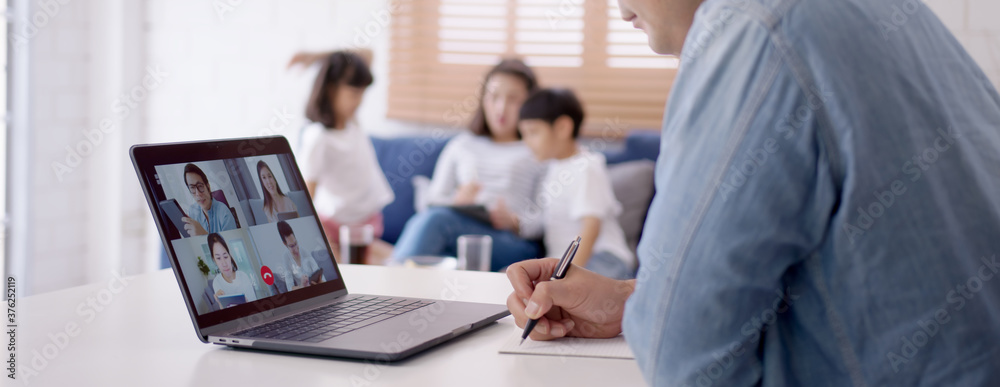 Fototapeta Asian business man stay with family and work remotely at home video conference remote call to corporate group. Meeting online,videocall, group discuss online concept.