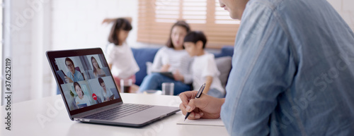 Obraz Asian business man stay with family and work remotely at home video conference remote call to corporate group. Meeting online,videocall, group discuss online concept. - fototapety do salonu
