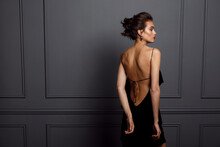 Back View Of A Sensual Brunette Young Woman In Sexy Black Dress With Bare Back And Beautiful Earrings Nar Grey Dark Neoclassical Wall.