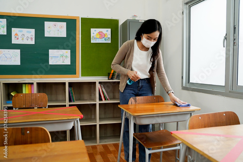 Young female teacher using an alcohol spray to disinfect student desks in classroom Fototapeta