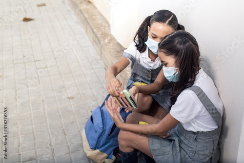 Photo Primary school girls sitting and wearing face mask on the schoolyard showing new material supplies