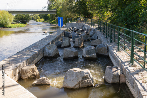 Slika na platnu Fish ladder, fishway, fish pass or fish steps passage though weir crossing on a