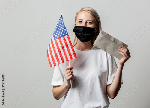 Fototapeta Blonde girl in face mask with USA flag and money on white background obraz
