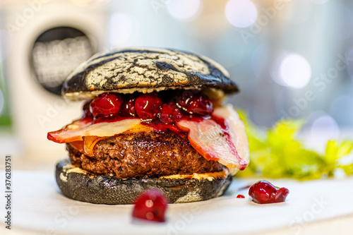 A black Burger with bacon and berry sauce is on the table. © milanchikov