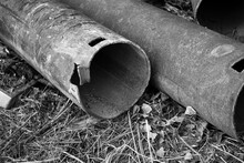 Replacement Of Old Pipes With New Ones. On The Ground In The Grass Lie Old Water Pipes With Traces Of Rust. Black And White Image.