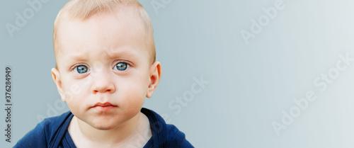 Canvastavla Beautiful one year old baby boy with blue eyes isolated on blue background