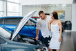 A young couple chooses a new car at the dealership and consults with a representative of the dealership. Used cars for sale. Dream fulfillment