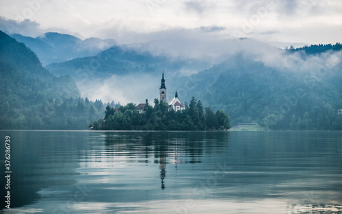 Fotografiet Lake Bled early in the morning, Bled island with small pilgrimage Church of the Assumption of Maria, foggy mountains in the background, Slovenia, Europe