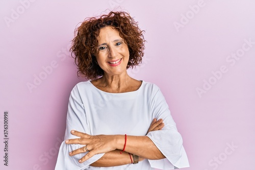 Beautiful middle age mature woman wearing elegant clothes over pink background happy face smiling with crossed arms looking at the camera Billede på lærred