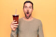 Young Handsome Man Drinking Cola Refreshment Beverage Over Isolated Yellow Background Scared And Amazed With Open Mouth For Surprise, Disbelief Face
