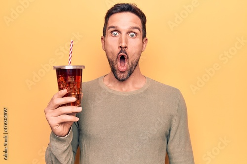 Tela Young handsome man drinking cola refreshment beverage over isolated yellow backg