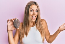 Young Blonde Woman Holding Pumice Stone Celebrating Achievement With Happy Smile And Winner Expression With Raised Hand
