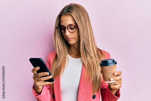 Young blonde woman using smartphone and drinking a cup of coffee relaxed with serious expression on face Canvas Print