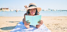 Young African American Woman On Vacation Laying On The Towel Reading Book At The Beach