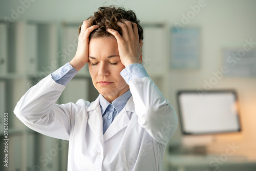 Young tired female chemist or pharmacist in whitecoat touching her head #376308553
