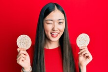 Young Chinese Woman Eating Healthy Rice Crackers Winking Looking At The Camera With Sexy Expression, Cheerful And Happy Face.