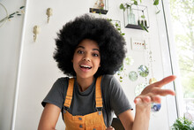 Young African American Hipster Woman With Afro Hair Looking At Webcam Talking To Camera With Friend Online Sitting At Cafe Table Making Video Call, Virtual Chat, Recording Blog, Headshot Portrait.