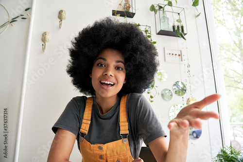 Obraz Young African American hipster woman with Afro hair looking at webcam talking to camera with friend online sitting at cafe table making video call, virtual chat, recording blog, headshot portrait. - fototapety do salonu