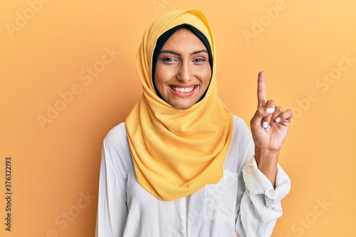 Young brunette arab woman wearing traditional islamic hijab scarf showing and pointing up with finger number one while smiling confident and happy Canvas Print