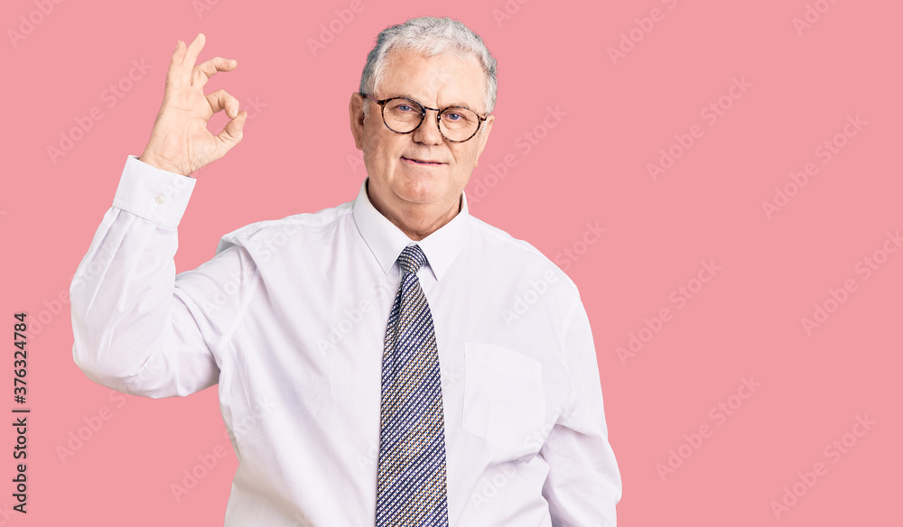 Fototapeta Senior grey-haired man wearing business clothes smiling positive doing ok sign with hand and fingers. successful expression.
