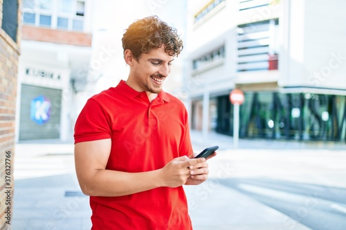 Young handsome caucasian man smiling happy using smartphone walking at city Wallpaper Mural