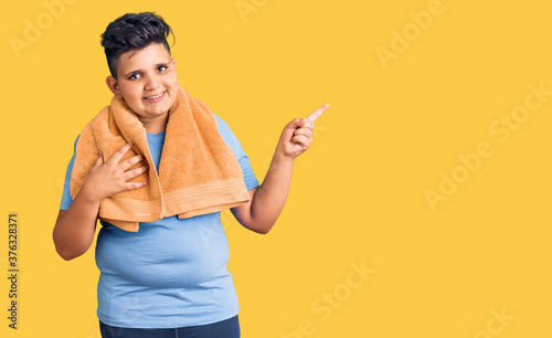 Little boy kid wearing sportswear and towel smiling happy pointing with hand and Fotobehang