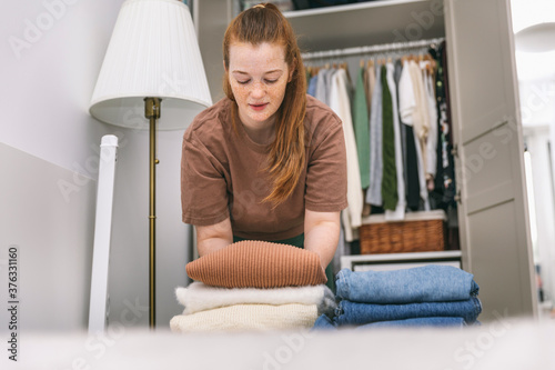 Woman folds in a stack of sweaters and jeans Fototapeta