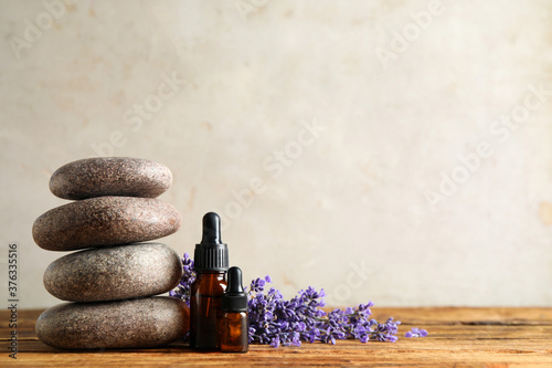 Fotografie, Obraz Bottles of essential oil, spa stones and lavender flowers on wooden table