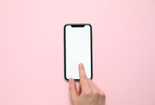 MYKOLAIV, UKRAINE - JULY 07, 2020: Woman Using IPhone 11 On Pink Background, Top View. Mockup For Design
