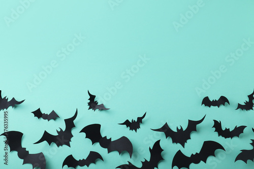 Many black paper bats on light blue background, flat lay with space for text. Halloween decor