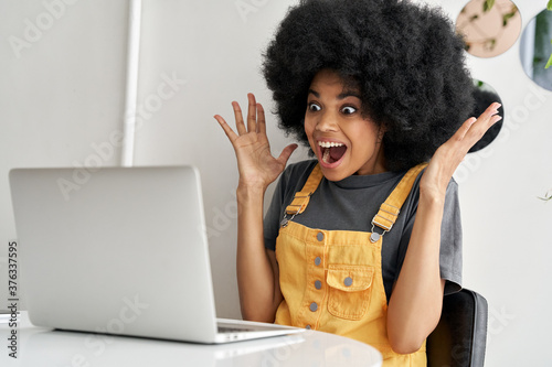 Valokuva Excited happy hipster African American woman winner, female student looking at laptop laptop feeling amazed looking at computer winning online bid, reading great news, passed exam getting good result