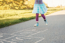 Closeup Of Child Girl Playing Jumping Hopscotch Outdoors. Funny Activity Game For Kids On Playground Outside. Summer Backyard Street Sport For Children. Happy Childhood Lifestyle.