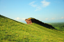 Remains Of An Ancient Wall On Top Of A High Grassy Hill.