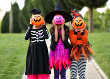 Unrecognizable Girls Hiding Faces Behind Trick Or Treat Baskets