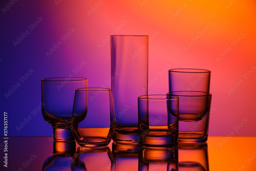 Fototapeta Empty glasses on color background