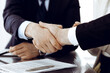 Business people shaking hands after contract signing in modern office. Teamwork, partnership and handshake concept