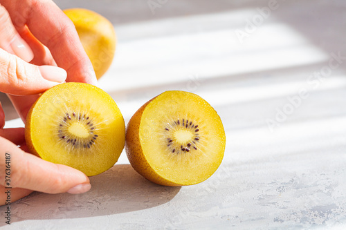 Carta da parati Ripe sliced yellow kiwi halves on gray background.