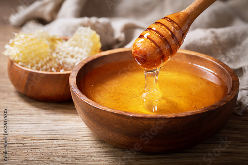 Foto pouring honey into wooden bowl