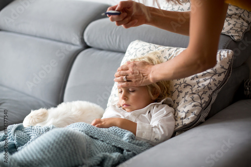 Sick child, toddler boy lying on the couch with his white puppy in living room with fever, resting