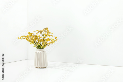 White simple vase with yellow flowers, front view Canvas-taulu
