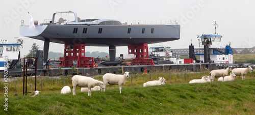 Transport of a super yacht on a pontoon with tugboats at the river Fototapete