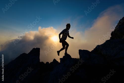 Silhouette of man on rocky ridge in mountain running uphill Wallpaper Mural