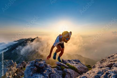 Photo Sky runner man uphill on rocks at sunset